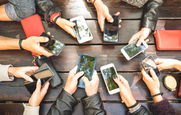 people group having addicted fun together using smartphones - detail of hands sharing content on social network with mobile smart phones - technology concept with millennials online with cellphones - dispositivo informatico portatile foto e immagini stock