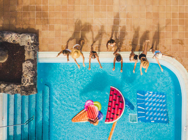 People group of young women have fun in summer holiday at the pool playing with coloured trendy inflatable mattress lilo - viewed from high top aerial - friends enjoy the hotel resort party lifestyle stock photo