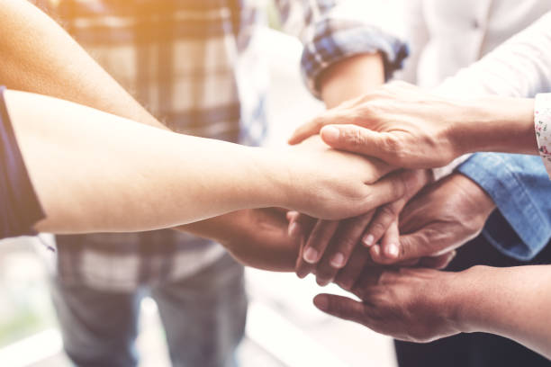 people hand assemble as a connection meeting teamwork concept. group of people colleague assembly hands as a business or work achievement. man and women touch each other hands. teamwork conceptual. - społeczność zdjęcia i obrazy z banku zdjęć