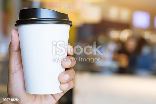 people hand holding paper cup of take away drinking coffee show on clear sky blue natural morning sunlight. space Place for your text or logo. empty space for text.