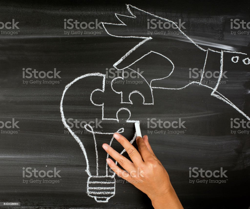 People Hand Put A Part Of Light Bulb Puzzle stock photo