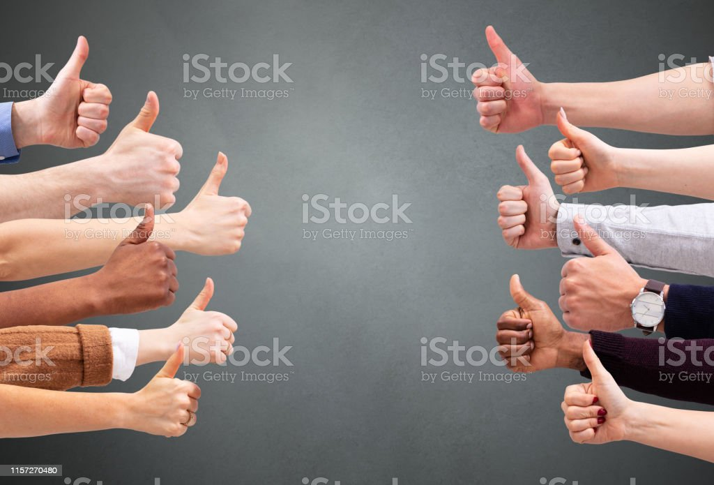 Close-up Of People\'s Hand Showing Thumb Up Sign Over Green Backdrop