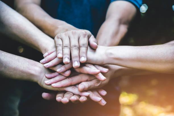 사람들은 연결 회의 팀워크 개념으로 조립손을 합니다. 비즈니스 또는 작업 성과로 손을 조립하는 사람들의 그룹. 남자와 여자는 야외에서 서로 손을 만지고 있습니다. 팀워크 개념. - double exposure 뉴스 사진 이미지