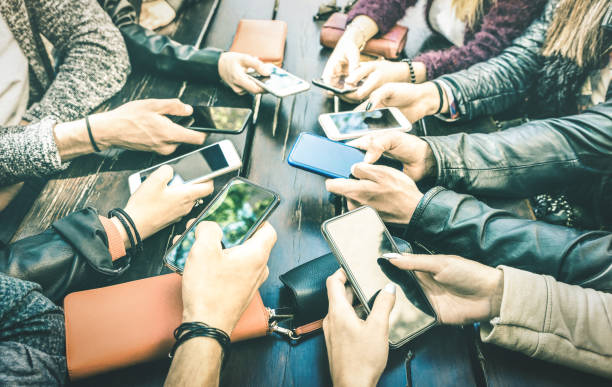 People hands having addicted fun together using smartphone - Millenial sharing content on social media network with mobile smart phones - Technology concept with millennials online on cellphone device stock photo