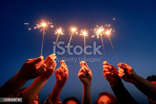 Close up of young people hands holding sparklers against sky.