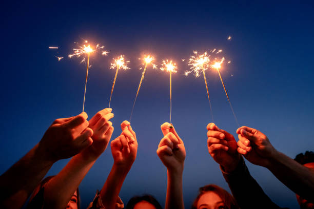 people hands holding sparklers against sky. stock photo