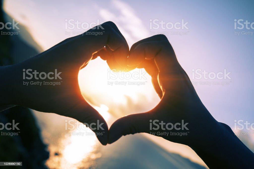 people hands making heart shape in sky – zdjęcie