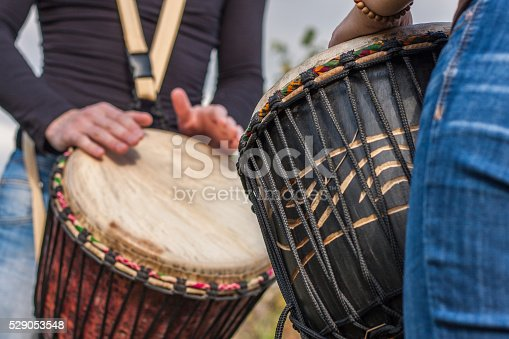182677415 istock photo People hands playing music at djembe drums 529053548