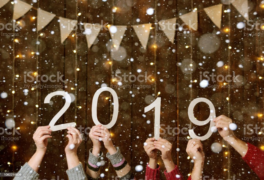 people hands showing 2019 numbers on wooden background - new year holiday concept stock photo