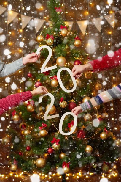 manos de la gente mostrando 2020 números sobre fondo de madera - nuevo año concepto de vacaciones - foto de stock