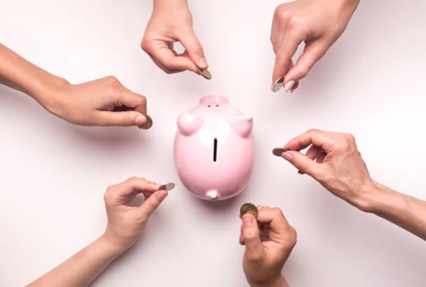 Menschen Hände werfen Münzen in Sparschwein für Crowdfunding – Foto