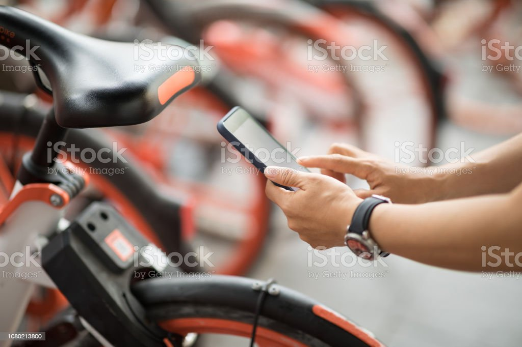 People hands using smartphone scanning the QR code of shared bike in city – zdjęcie