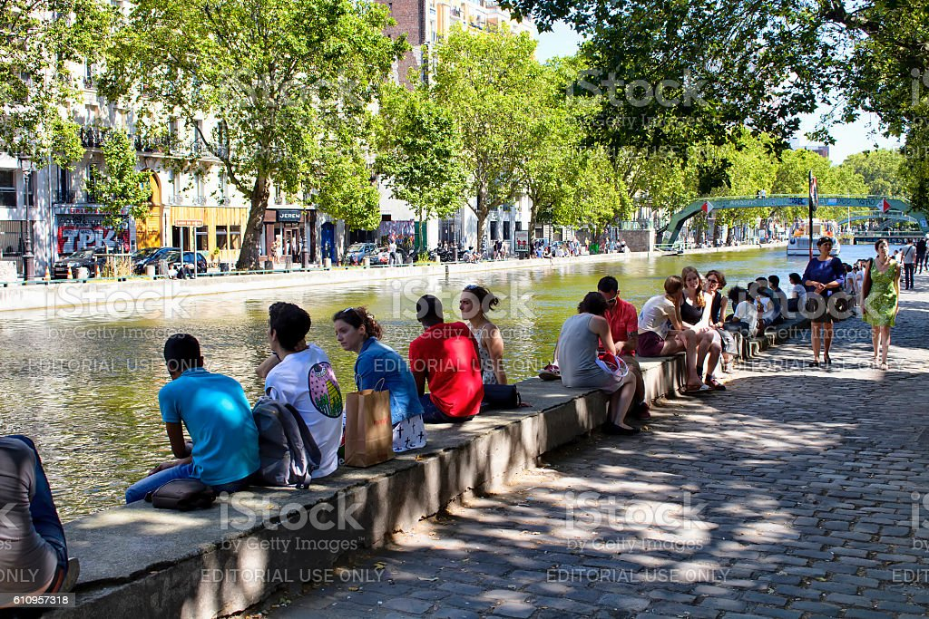 People hang out by Canal Saint Martin stock photo