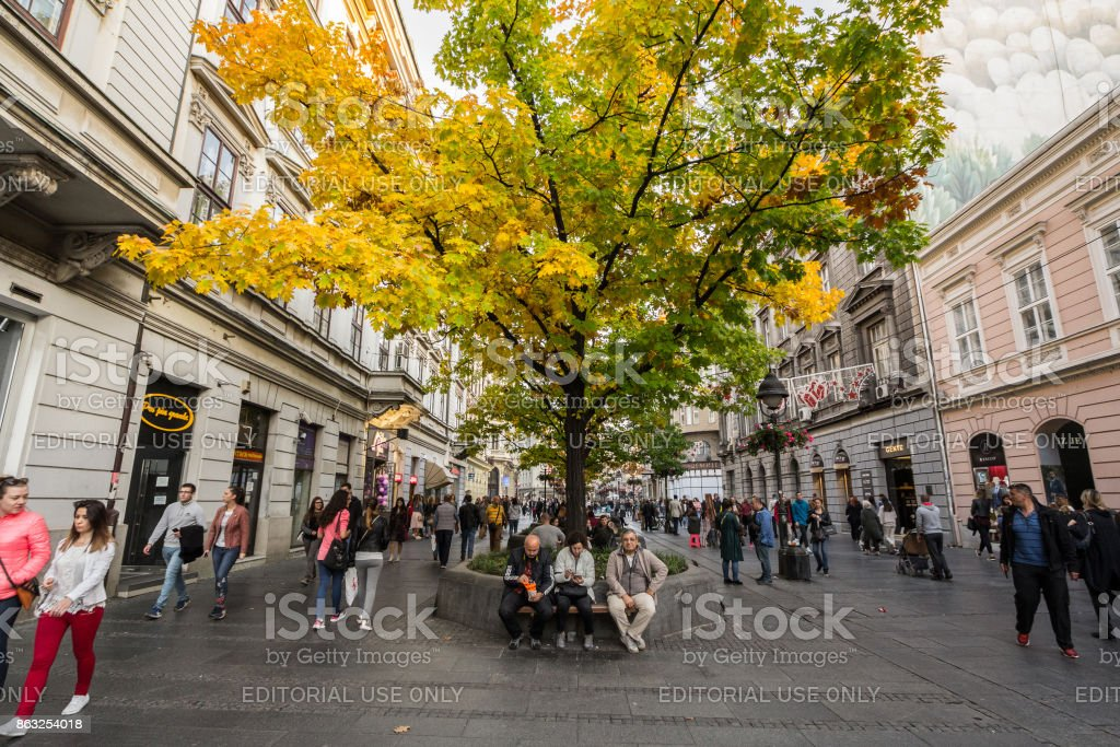 People having a break on a bench under a tree wearing autumn colors on Kneza Mihailova, the main pedestrian street of Belgrade stock photo