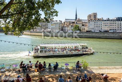 istock People having a drink in the shade of a tree in an open-air cafe along the Seine during Paris-Plage summer event, with a tour boat passing by and Notre-Dame de Paris cathedral in the background. 1016120194