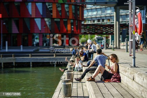 Gothenburg, Sweden - May 16, 2019 : People having a sun bathing side by Lindholmen Ferry Port in summer time