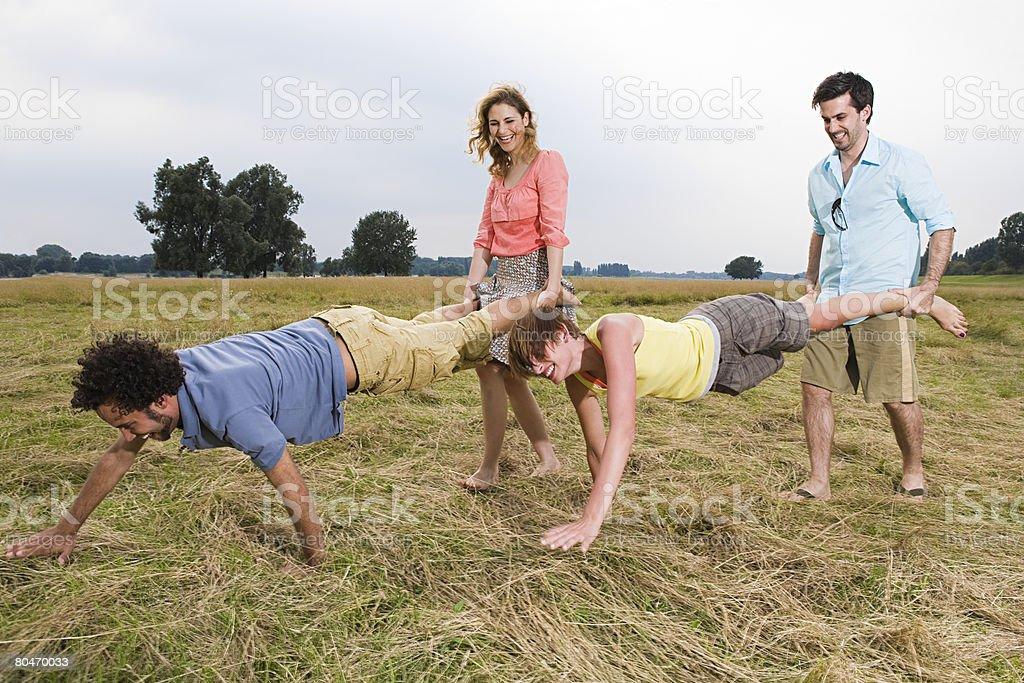 People having a wheelbarrow race stock photo