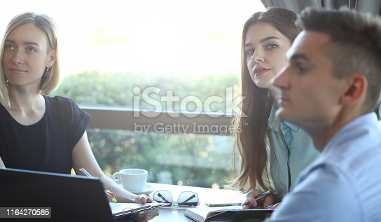 Portrait of three partners drinking coffee and negotiating contract. Two female and man communicating with each other. Restaurant interior. Blurred background