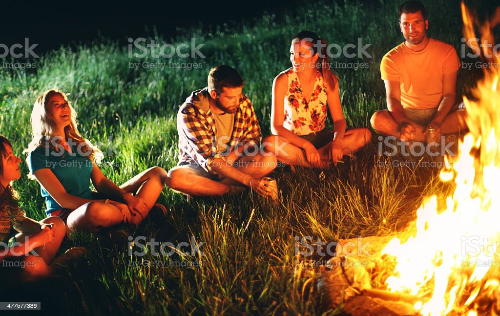 Group of five young people sitting by campfire and having fun.There...