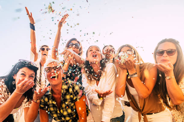People having fun in party celebration friends concept - group of young and adult women all together laughing blowing coloured confetti - friendship and love for lifestyle with mixed active generations stock photo