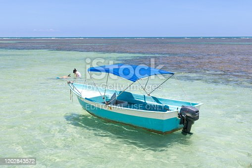 Bahia, Brazil - January 2020: Boat in the middle of natural pools in the ocean and people diving. Morro de Sao Paulo, Salvador, Brazil. Hill.