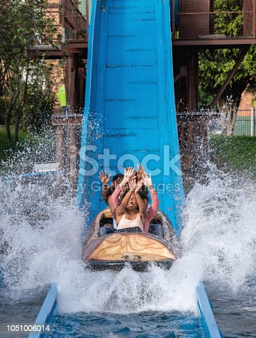 Group of people having fun on a water ride at an amusement park and getting wet - lifestyle concepts