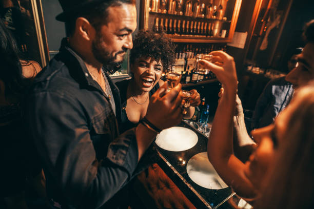 People having fun with drinks at nightclub Happy young people having fun with drinks at nightclub. Man and women drinking at bar. tequila shot stock pictures, royalty-free photos & images
