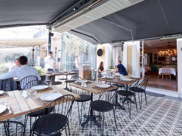 menschen, die in ein schickes restaurant zu mittag - outdoor esszimmer stock-fotos und bilder