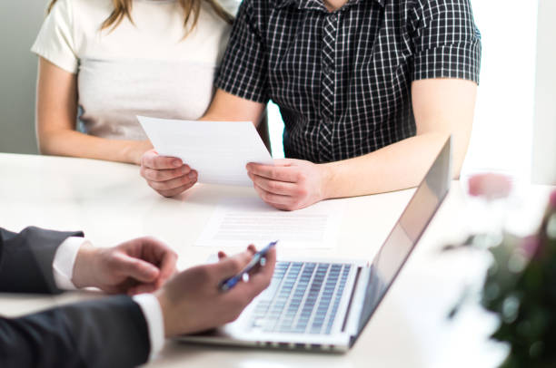 People having meeting about mortgage, bank loan, buying house, insurance or apartment rent. Woman, man and lawyer preparing prenupitial agreement in office. stock photo