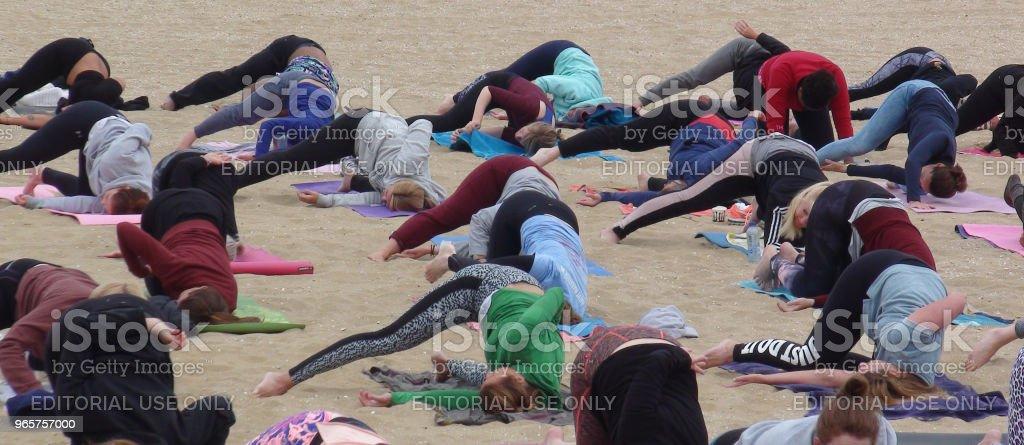 Mensen die ontspanning Yoga oefening scène op het strand - Royalty-free Buigen - Lichaamsbeweging Stockfoto