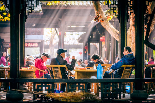 People having tea in People's park, Chengdu Chendu, China - Nov 1, 2017 : People sitting on bamboo chairs and having tea in People's park famous HeMing teahouse with sunrays in the background. tea room stock pictures, royalty-free photos & images