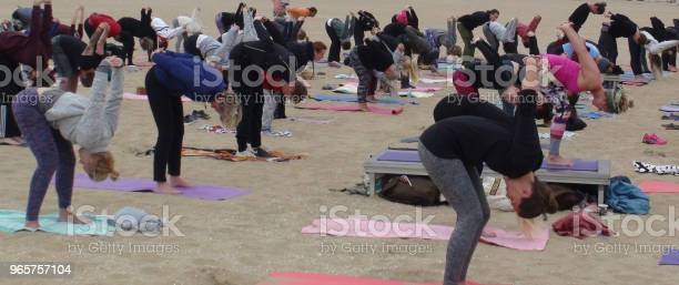 People Having Yoga Exercise For Health And Relaxation At Seashore — стоковые фотографии и другие картинки Гаага