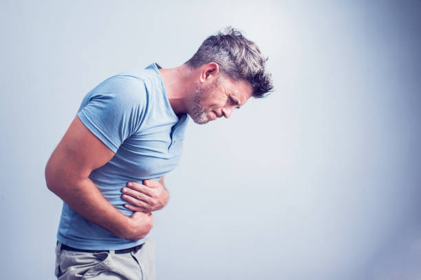 People, healthcare and health problem concept - unhappy man suffering from stomach ache over gray background stock photo