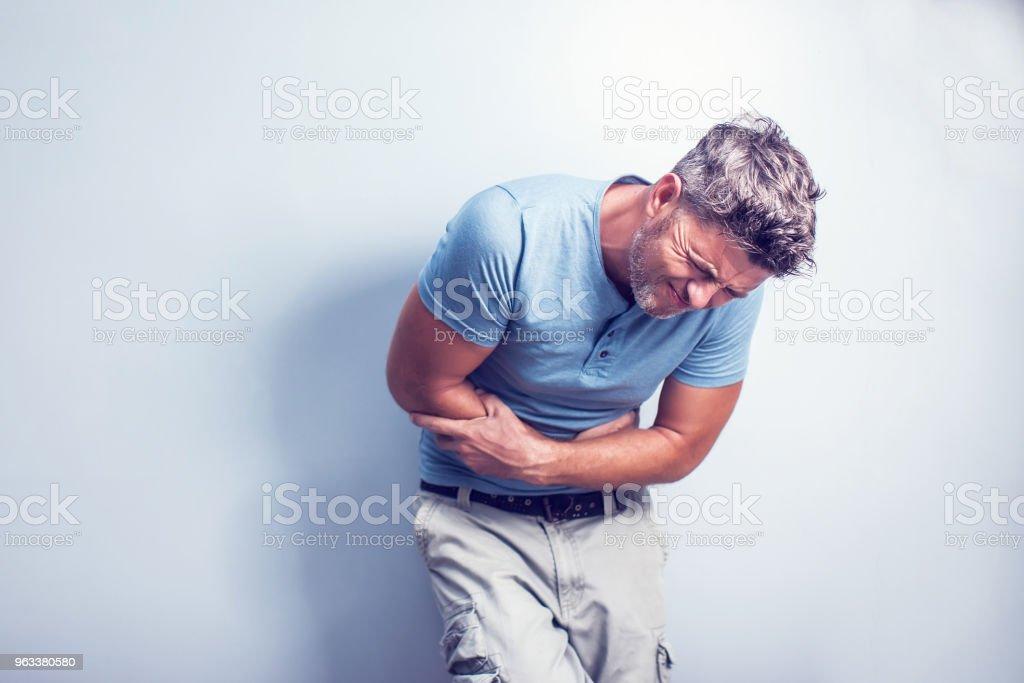 Notion de problème personnes, la santé et la santé - malheureux homme souffrant de maux d'estomac sur fond gris - Photo