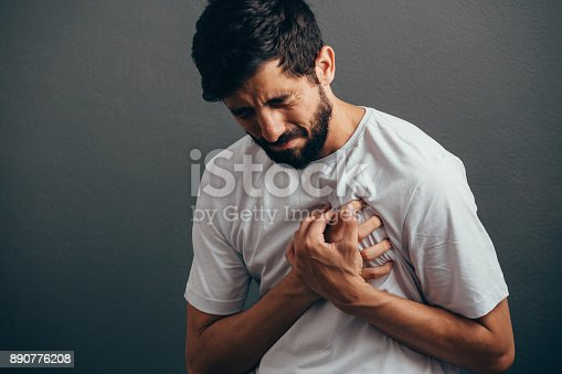 istock People, healthcare and problem concept - close up of man suffering from heart ache over gray background 890776208