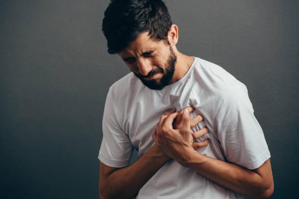 Conceito de pessoas, cuidados de saúde e problema - close-up do homem que sofre de dor no coração sobre fundo cinza - foto de acervo