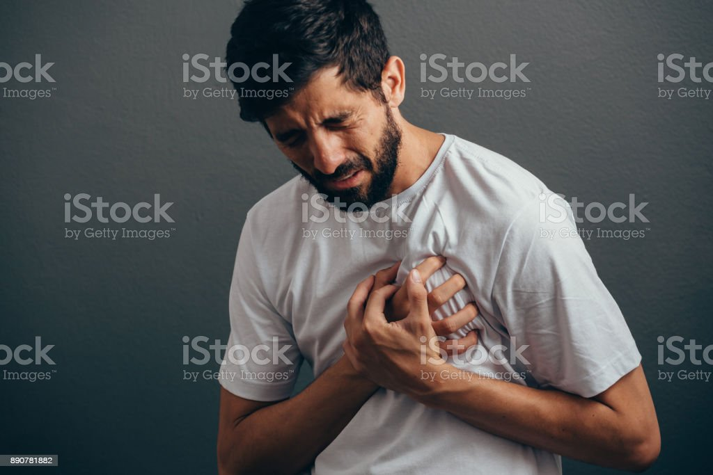 People, healthcare and problem concept - close up of man suffering from heart ache over gray background stock photo
