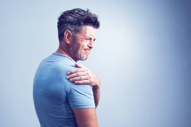 conceito de pessoas, cuidados de saúde e problema - infeliz homem que sofre de dor no pescoço ou ombro em casa - ombro - fotografias e filmes do acervo