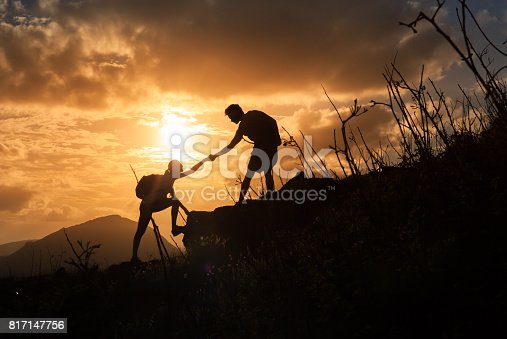 istock People helping each other hike up a mountain at sunrise. 817147756