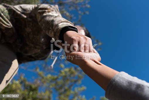 istock People helping each other hike up a mountain 915623632
