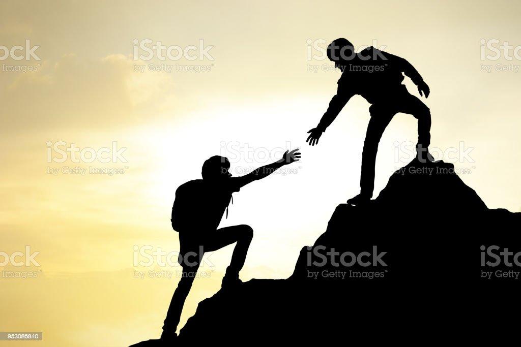 People helping on peak mountain and sunrise background climbing team...
