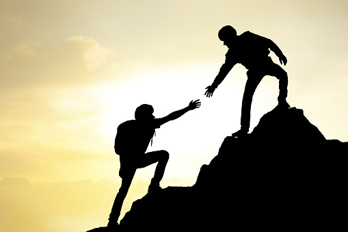 istock People helping on peak mountain and sunrise background climbing team work success business concept 953086840