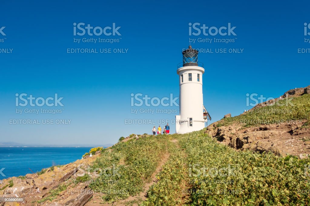 People hike at lighthouse on Anacapa Island in Channel Islands National Park California stock photo
