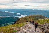 Ben Nevis / UK - August 24 2019: People hike on the highest mountain in Britain, Ben Nevis. Fort William (and some other Scottish villages), Loch Linnhe and Loch Eil are in the background.