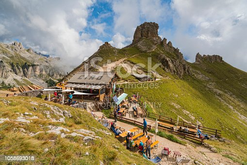 istock People, hikers resting at rifugio Poda di Vael cottage rest place on roundabout path from Ciampedie ropeway under the mighty spiers of Vaiolet in  Dolomites, Northern Italy. 1058693018