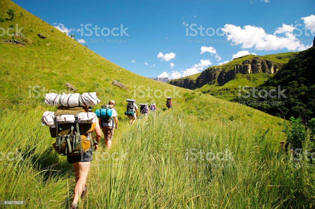 People hiking mountains rucksack boots camping Drakensberg grass hills sky stock photo