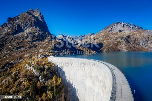 524621933 istock photo People hiking on a top of a dam in a beautiful autumnal landscape of Swiss Alps, Valais, Emosson, Switzerland, Europe. 1183811074