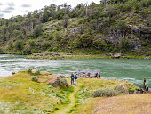 People walking on trail of Paseo de la isla, Island hike, along Lapataia River in Tierra del Fuego National Park, Patagonia, Argentina