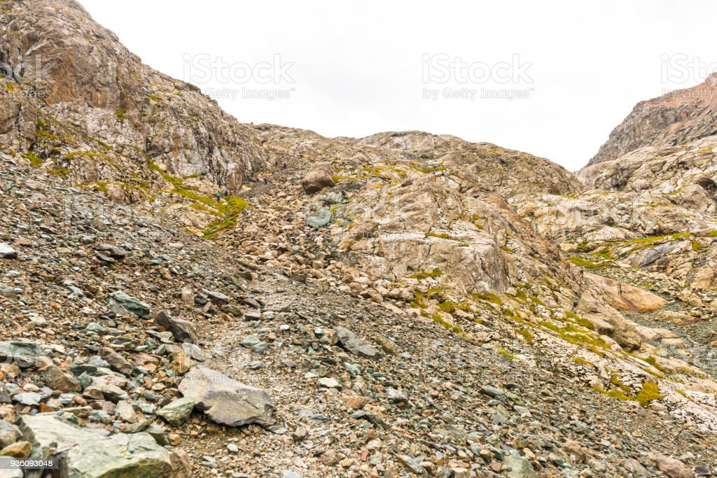 People hiking up steep rocky mountain in Kyrgyzstan stock photo