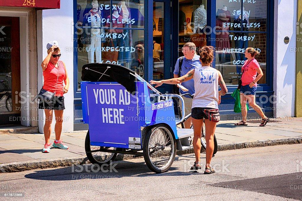 People hiring a pedicab on Meeting Street in Charleston SC stock photo